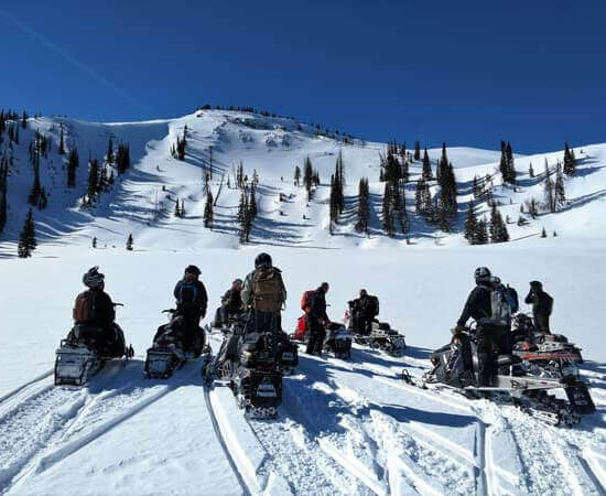 snowmobile guide learning about avalanche safety
